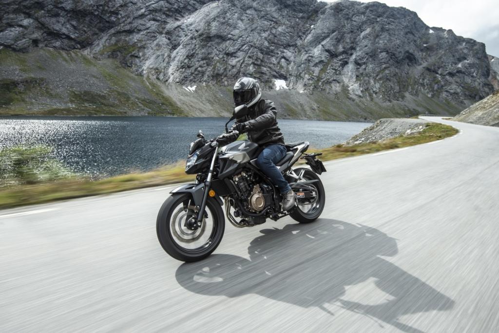 Honda CB500F som kjører på en vei langs fjell og fjord